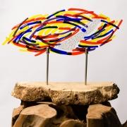 Kleurrijk, abstract herinneringsbeeld waarbij de as zichtbaar in het gedenkobject is verwerkt