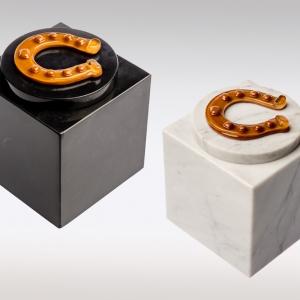 Witte en zwarte marmeren urn met bruine paardenhoef van glas