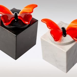 Witte en zwarte marmeren urn met oranje vlinder van glas