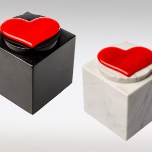 Witte en zwarte marmeren urn met rood hart van glas