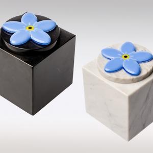 Witte en zwarte marmeren urn met vergeet me nietje van glas