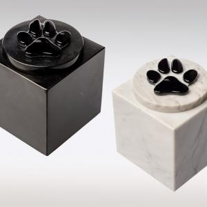 Witte en zwarte marmeren urn met zwart hondenpootje van glas